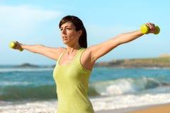 Donna di forma fisica che risolve sulla spiaggia Fotografie Stock