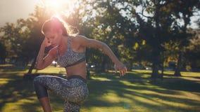 Donna di forma fisica che si scalda al parco un giorno soleggiato Immagine Stock Libera da Diritti