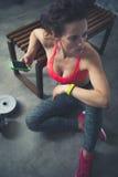 Donna di forma fisica che si siede nella palestra del sottotetto con il telefono cellulare Fotografie Stock Libere da Diritti