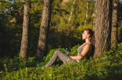Donna di forma fisica che si siede vicino ad un albero nel legno che riposa dopo un allenamento Sport, forma fisica, concetto di  Immagini Stock Libere da Diritti