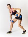 Donna di forma fisica che solleva i pesi liberi Su una priorità bassa bianca Fotografie Stock