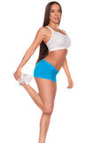 Donna di forma fisica che sta contro il fondo bianco isolato fotografia stock