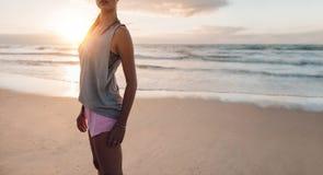 Donna di forma fisica che sta sulla spiaggia Immagini Stock