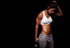 Donna di forma fisica che tiene la campana pesante del bollitore Immagini Stock Libere da Diritti