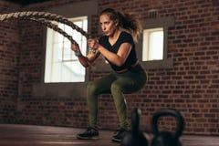 Donna di forma fisica che usando le corde di battaglia per esercitarsi fotografie stock libere da diritti