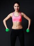 Donna di forma fisica in cima rosa e pantaloni neri che fanno worko delle teste di legno Fotografia Stock Libera da Diritti
