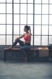 Donna di forma fisica con il telefono cellulare che si siede nella palestra del sottotetto Fotografia Stock Libera da Diritti