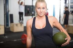 Donna di forma fisica con la palla di colpo al centro della palestra Fotografia Stock