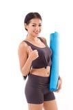 Donna di forma fisica con la stuoia di yoga della tenuta della mano, dante pollice su Fotografia Stock