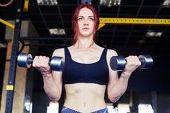 Donna di forma fisica con le teste di legno di sollevamento Fotografie Stock Libere da Diritti
