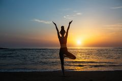 Donna di forma fisica di meditazione della siluetta di yoga sull'oceano fotografia stock