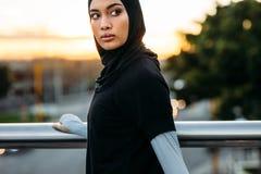Donna di forma fisica nel hijab che sta all'aperto nella mattina immagini stock libere da diritti