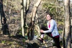 Donna di forma fisica nella foresta che allunga le gambe prima del pareggiare Immagine Stock Libera da Diritti