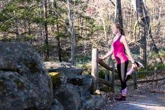 Donna di forma fisica nella foresta che allunga le gambe prima del pareggiare Fotografia Stock Libera da Diritti