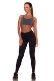 Donna di forma fisica nello stile di sport che sta contro il fondo bianco isolato fotografie stock
