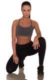 Donna di forma fisica nello stile di sport che sta contro il fondo bianco isolato fotografia stock libera da diritti