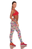Donna di forma fisica nello stile di sport che sta contro il fondo bianco isolato fotografia stock