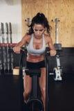 Donna di forma fisica sulla bicicletta che fa cardio allenamento alla palestra Immagini Stock Libere da Diritti