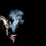 Donna di fumo nell'oscurità Fotografia Stock Libera da Diritti