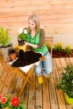 Donna di giardinaggio che pianta il fiore della sorgente Immagini Stock