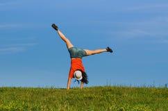 Donna di ginnastica che fa cartwheel sugli ambiti di provenienza della natura Fotografia Stock