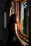Donna di Goth che osserva fuori finestra Immagini Stock