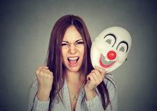 Donna di grido arrabbiata che decolla la maschera del pagliaccio che esprime felicità fotografia stock libera da diritti