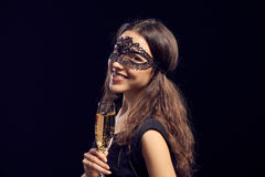 Donna di Happe nella maschera che giudica di vetro con champagne Immagine Stock Libera da Diritti
