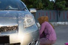 Donna di Hijab che pulisce il cappuccio dell'automobile all'area di aria aperta fotografia stock libera da diritti