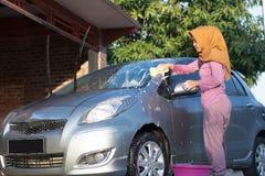 Donna di Hijab che pulisce il parabrezza all'area di aria aperta fotografia stock libera da diritti