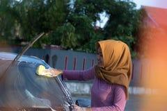 Donna di Hijab che pulisce il parabrezza all'area di aria aperta fotografia stock
