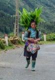 Donna di Hmong che cammina sulla strada della montagna fotografia stock libera da diritti