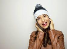Donna di inverno con il cappello della lana con il fiocchetto che sorride alla macchina fotografica su fondo grigio con copyspace Fotografie Stock