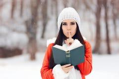 Donna di inverno con il dito sulle sue labbra che tengono un libro Fotografia Stock