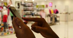 donna di 4k A che per mezzo di uno smartphone contro il negozio di vestiti, il centro commerciale & il supermercato stock footage