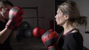Donna di kickboxing e un uomo che inscatola insieme come raccomandazione di terapia di distensione della tensione allentare le te archivi video