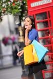 Donna di Londra che parla acquisto felice dello Smart Phone Fotografie Stock