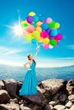 Donna di lusso di modo con i palloni a disposizione sulla spiaggia contro Fotografia Stock Libera da Diritti