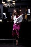 Donna di lusso sola nel basamento viola del vestito alla barra Fotografia Stock
