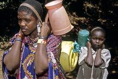 Donna di Maasai ed acqua potabile di trasporto del bambino Fotografie Stock Libere da Diritti