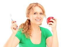 Donna di Maturesmiling che tiene una mela e uno spazzolino da denti rossi Fotografie Stock Libere da Diritti