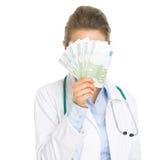 Donna di medico che si nasconde dietro il fan degli euro Immagini Stock