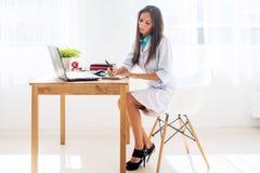 Donna di medico che si siede allo scrittorio ed al lavoro Immagini Stock