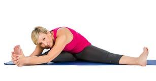 Donna di medio evo che fa gli esercizi di yoga Immagini Stock