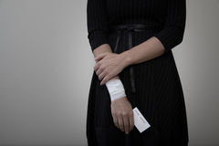 Donna di medio evo che mostra il suo polso bendato Fotografia Stock