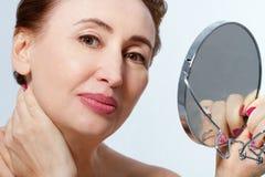 Donna di medio evo con lo specchio, toccante il suo collo Macro fronte femminile menopause Collagene antinvecchiamento fotografie stock