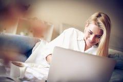 Donna di medio evo a letto facendo uso del computer portatile Fotografia Stock