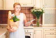 Donna di medio evo nella cucina con il sacchetto della spesa di carta pieno di fotografia stock libera da diritti