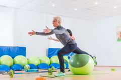 Donna di mezza età attiva che risolve con la palla di stabilità che partecipa alla classe di forma fisica del gruppo Immagini Stock Libere da Diritti