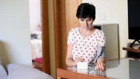 Donna di mezza età che misura la sua propria pressione sanguigna con un dispositivo elettronico di misura di pressione sanguigna archivi video